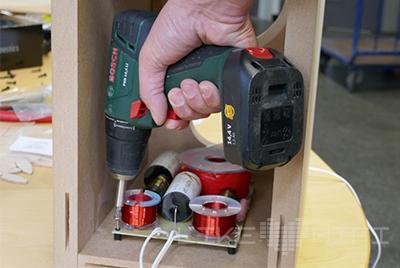Bevor die Box geschlossen wird, befestigen wir die Frequenzweiche mit ein paar Schrauben auf dem Boden