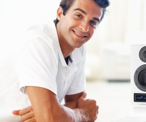 Portrait of handsome young man smiling using laptop at table